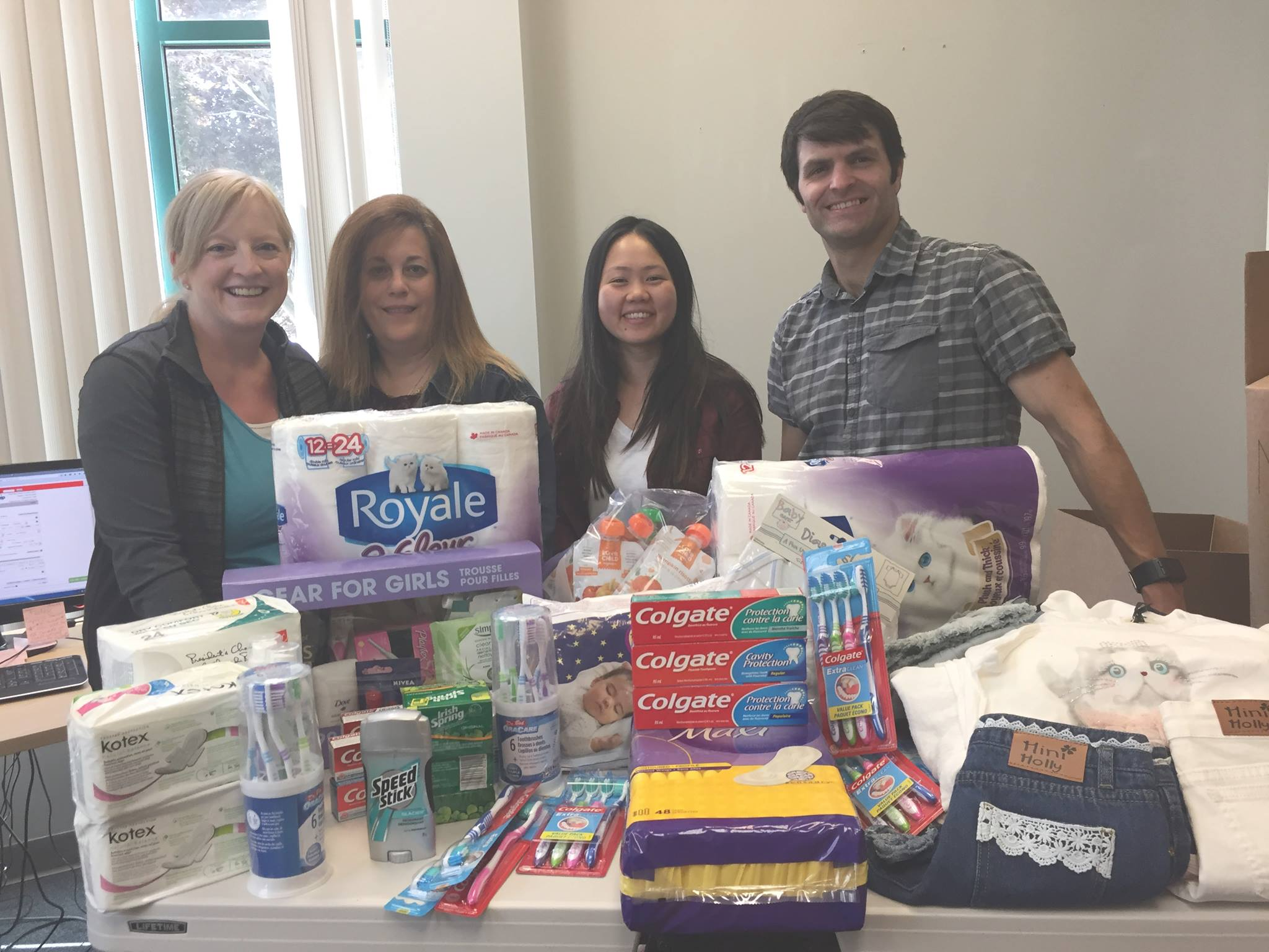Staff in front of table with donated products